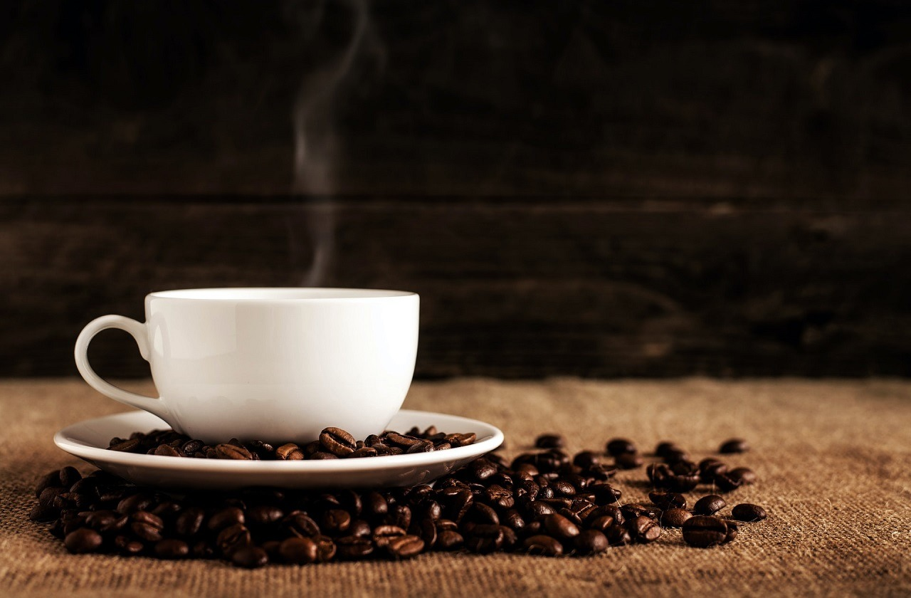 hot white cup of coffee with coffee beans